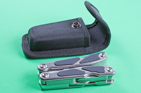 Folded multi tool with case on a green background Stock Photo - 12196746