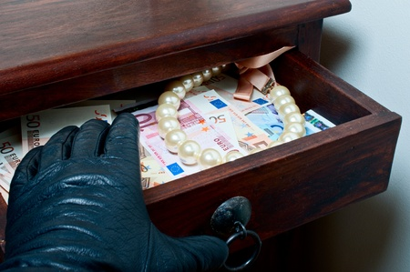 larceny: Black leather glove reaching money euro and pearls in drawer Stock Photo