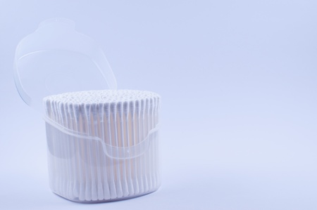 Cotton buds in open transparent plastic box with lid photo