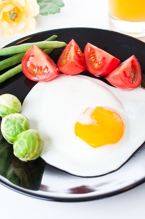 Fried egg with vegetables for breakfast on white background photo