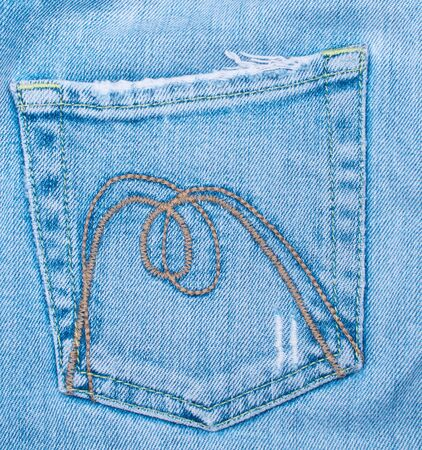 Old battered jeans pocket background close up photo