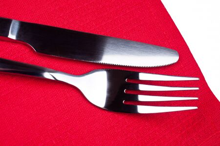 Knife and fork on red tablecloth close up photo