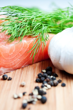 Salmon with black pepper and garlic on woode board close up photo