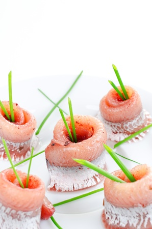 Rolls of marinated herring close up with spring onion on a plate photo