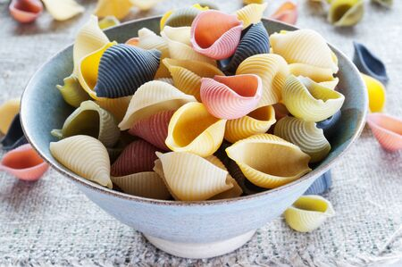 Multi colored pasta in bowl on a coarse cloth photo