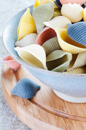 Pasta in bowl on a wooden board close up photo