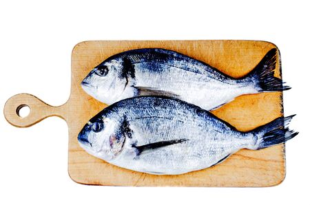 Two dorado on wooden board isolated photo
