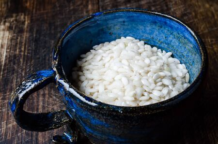 Uncooked risotto rice in blue cup on wooden table