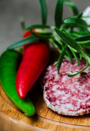 Peper salami and rosemary on cutting board close up photo