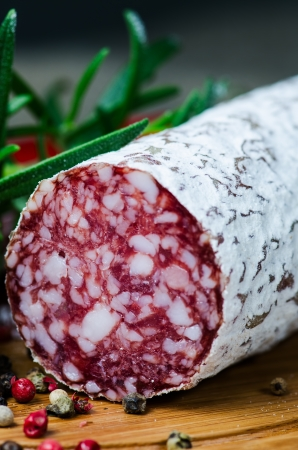 Close up salami peper corns rosemary on cutting board photo
