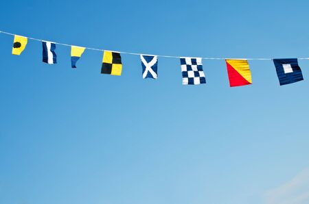 Nautical flags against blue sky photo