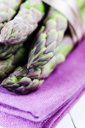 Bunch of asparagus on purple napkin close up