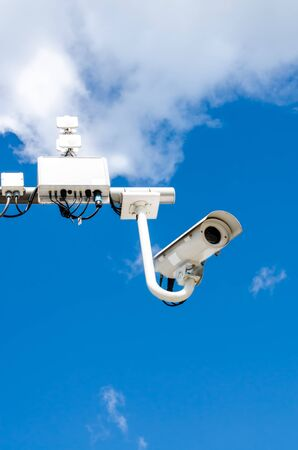 Surveillance camera on blue sky bacgroung photo