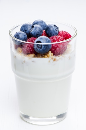 Yogurt with raspberries and blueberries in glass