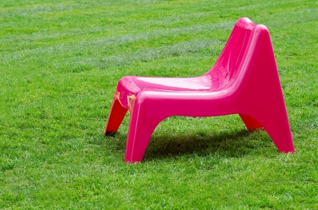 Pink chair on green grass background photo