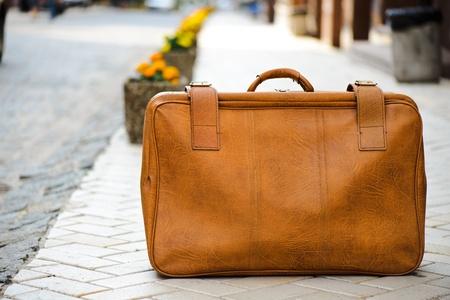 suitcases: Gedragen lederen koffer achtergelaten op een weg