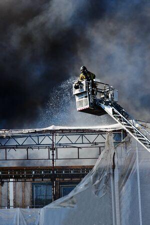 extinguishing: Fireman extinguishing fire on a building, Oslo, Norway