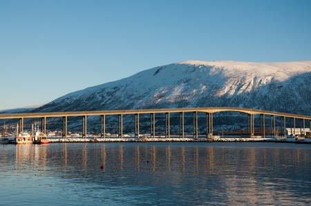 View of the Tromsoes bridge from the middle of the fjord photo