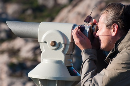 monocular: A man looking through a coin-operated monocular Stock Photo