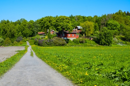 unpaved road: Unpaved road leading to red houses Stock Photo
