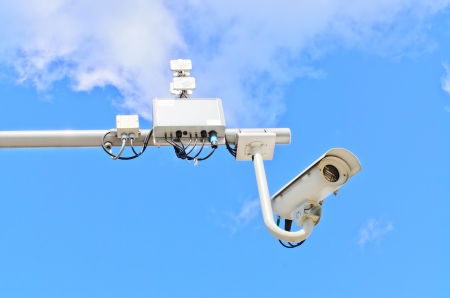 Surveillance cameras and surveillance equipment against blue sky photo