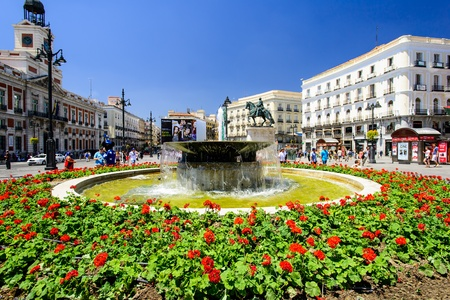 MADRID, JULY 12: Fountain and flowerbed at Puerta del Sol on July 12, 2012, Madrid, Spain. This is the centre (Km 0) of the radial network of Spanish roads.