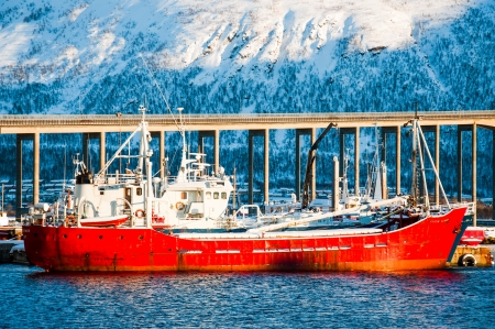 Red tanker is at anchor with bridge on background, Tromso, Norway