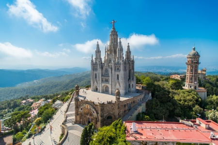Bird view on Tibidabo church on mountain in Barcelona with christ statue overviewing the city