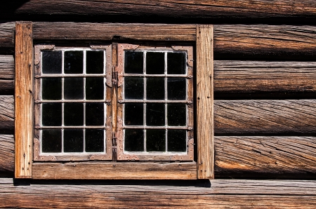 old building facade: Weathered log house wall window