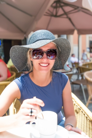 Beautiful young woman in hat and sunglasses at street cafe photo