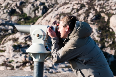 Man observing using spyglass on rocky background photo