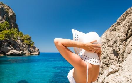 Jeune femme en chapeau blanc regardant la mer