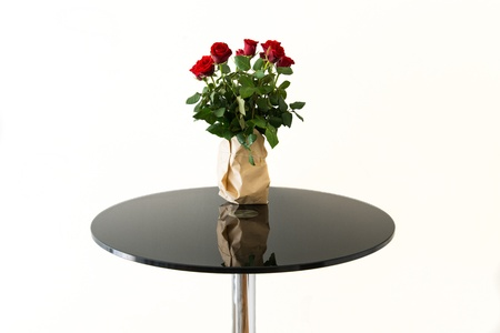 Bouquet of red roses in grey paper vase on black glass table isolated photo