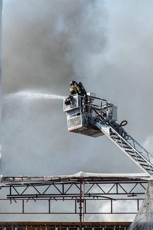 extinguishing: Firemen on a lift up extinguishing fire