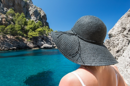 Young woman in black hat looking at sea photo