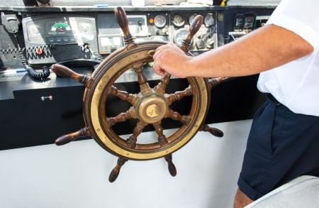 Captain hand on steering wheel of motor boat photo