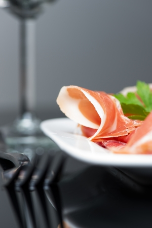 Prosciutto crudo with fresh herbs on plate