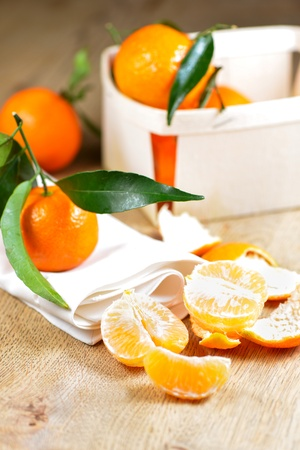 clementines: Pealed mandarin Oranges (Clementines) on wooden table