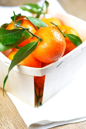 Mandarin Oranges (Clementines) close up in box on wooden table photo