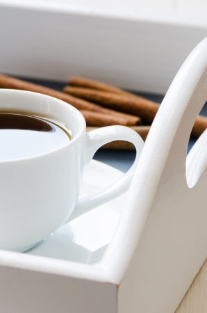 Cup of coffe on a tray with cinnamon sticks on background photo