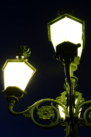 lit lamp: Decorative lit lamp post pictured at night