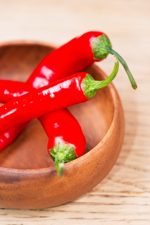 hottest: Fresh red  chili peppers on wooden bowl on table Stock Photo