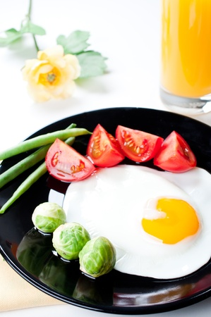 Vegetables and fried egg on white background photo