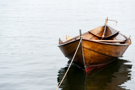 Old wooden row boat on water photo