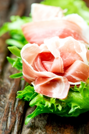 andalusian cuisine: Prosciutto and salad leaves on wooden old table