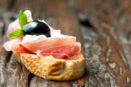 Sandwich with prosciutto, olive on wooden old table