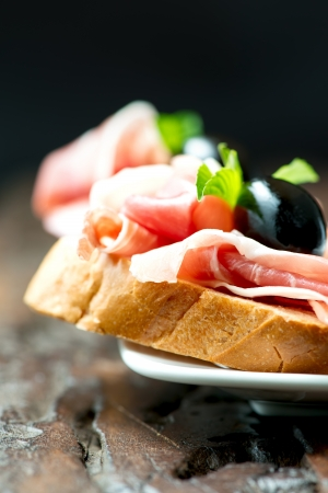 Sandwich with prosciutto, olive on plate