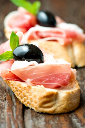 Sandwich with prosciutto, olive on wooden cutting board photo