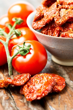 Fresh and dried tomatoes on old wooden table Stock Photo