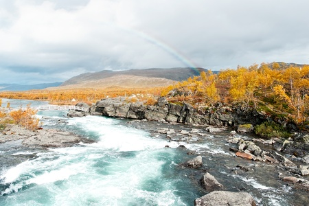 Mountain river in Norway with bridge and rainbow on background photo